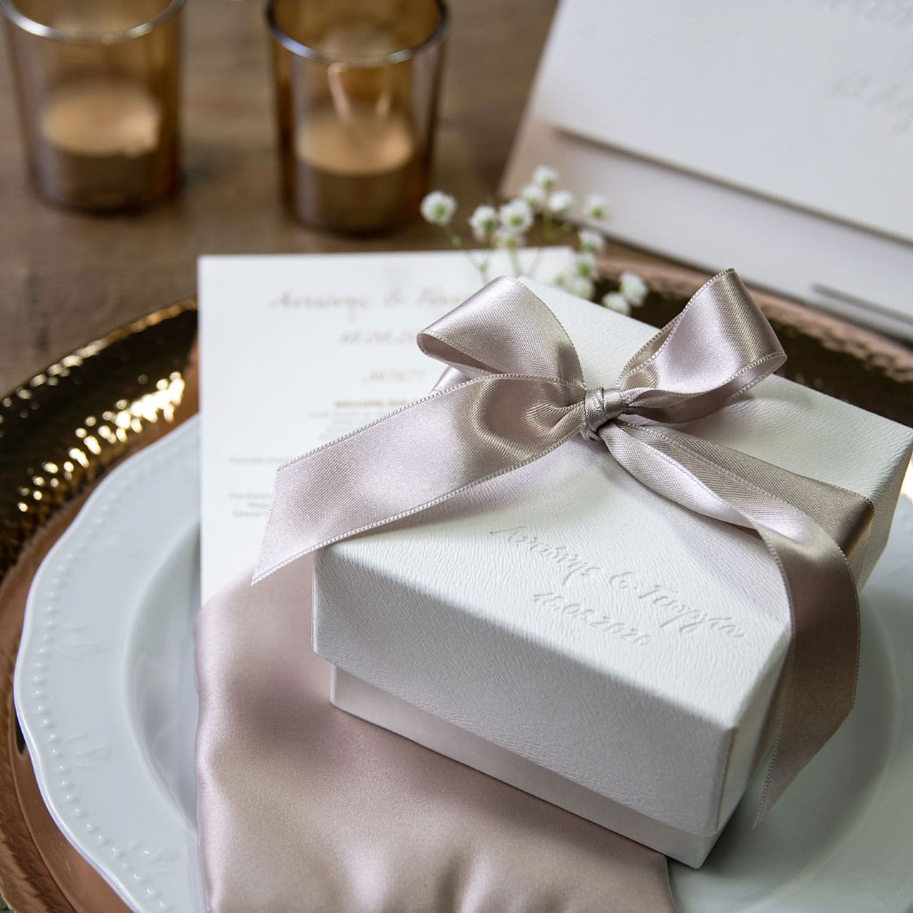 Κουτί μπομπονιέρα γάμου σε λευκό δέρμα με εκτύπωση βαθυτυπίας και σατέν κορδέλα στο χρώμα της άμμου